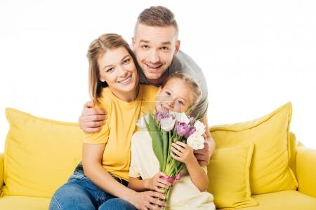 portrait of man hugging wife and little daughter with bouquet of tulips on yellow sofa isolated on white
