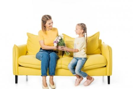 little kid giving bouquet of tulips to mother on yellow sofa isolated on white, mothers day holiday concept