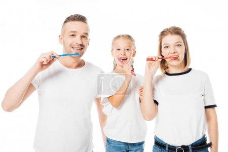 portrait of family in similar clothing brushing teeth isolated on white