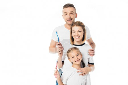 portrait of cheerful family in similar clothing with toothbrushes isolated on white