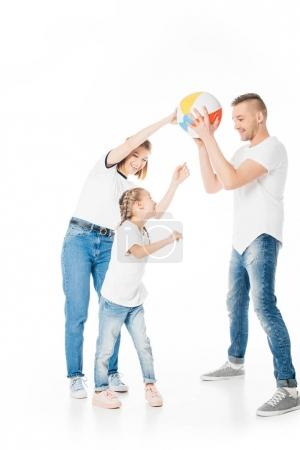 parents and kid in similar clothing playing with ball isolated on white