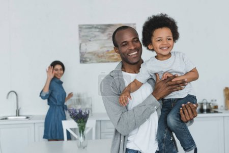african american father hugging son and mother waving hand at home