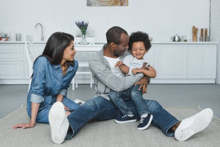 Photo for African american parents having fun with son on floor at home - Royalty Free Image