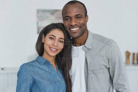 Photo pour Souriant afro-américaine copine et petit ami regardant la caméra à la maison - image libre de droit
