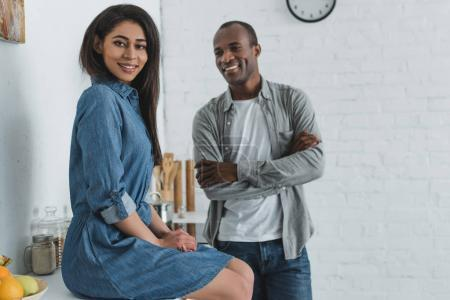 smiling african american girlfriend and boyfriend at kitchen