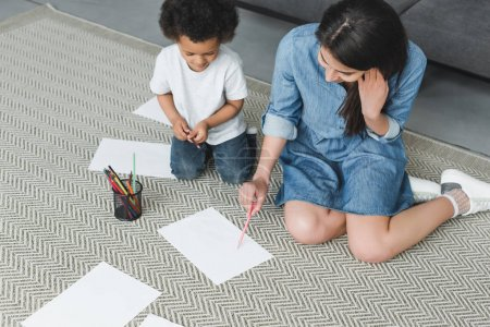 high angle view of african american mother and son drawing at home