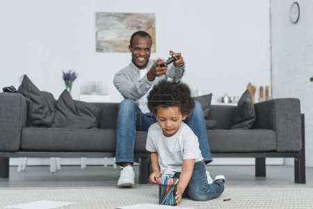 Photo for African american father playing video game and son drawing on floor at home - Royalty Free Image
