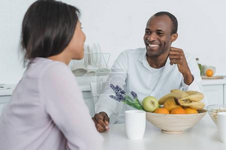 african american girlfriend and boyfriend sitting at table during breakfast