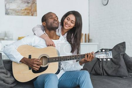 Photo for African american boyfriend playing guitar for happy girlfriend at home - Royalty Free Image