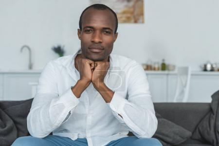 handsome african american man resting chin on hands and looking at camera at home