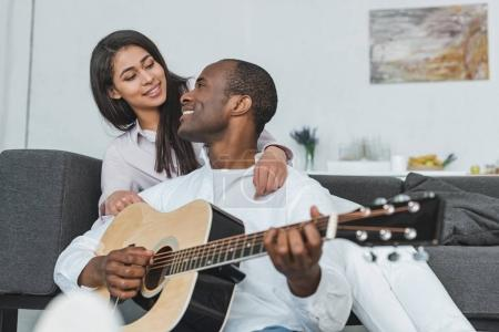Photo pour Sourire copain afro-américaine jouant de la guitare pour petite amie à la maison - image libre de droit