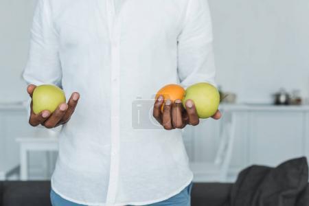 Photo pour Cropped image d'homme afro-américain, tenant les pommes et orange à la maison - image libre de droit