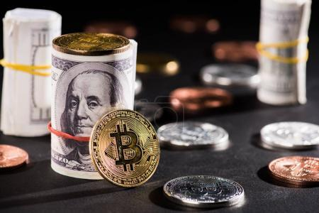 close-up view of rolled dollar banknotes and bitcoins on black