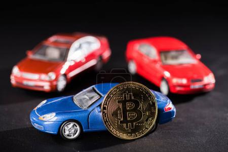 close-up view of bitcoin and car models on black
