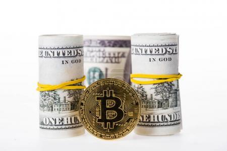 close-up view of rolled dollar banknotes and bitcoin isolated on white