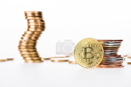 close-up view of bitcoin and stacked coins isolated on white