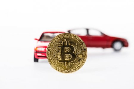 close-up view of bitcoin and car models isolated on white