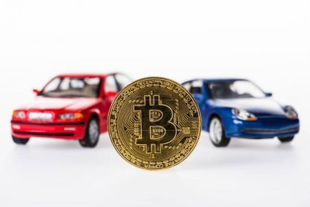 close-up view of bitcoin and car models on white