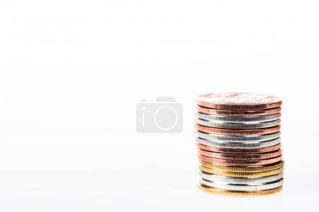close-up view of various stacked shiny coins isolated on white