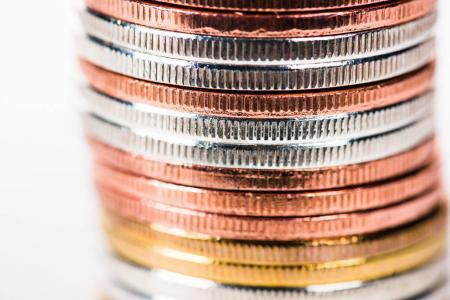 close-up view of shiny golden, silver and bronze stacked coins isolated on white
