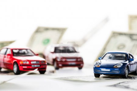close-up view of small car models and dollar banknotes on white