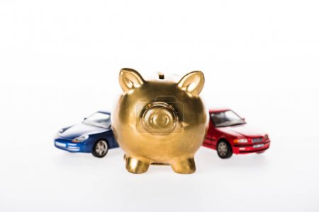 close-up view of golden piggy bank and small cars isolated on white