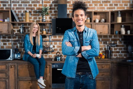 selective focus of smiling african american man with caucasian girlfriend sitting on counter behind in kitchen