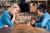 side view of multiethnic young couple playing chess together in kitchen