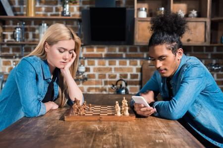 Photo for Side view of bored caucasian woman and african american man with smartphone at table with chess in kitchen - Royalty Free Image