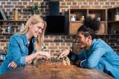 side view of smiling multiethnic young couple playing chess together in kitchen