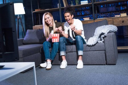 Smiling multiracial couple with popcorn watching sport match on sofa together at home
