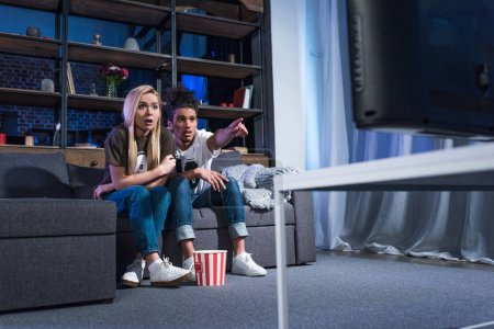 Scared multiracial couple with popcorn watching sport match on sofa together at home