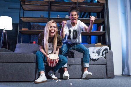 Happy multiracial couple with popcorn watching sport match on sofa together at home