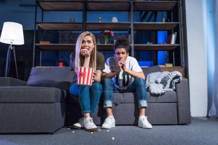 emotional young multiracial couple with popcorn watching horror film on sofa together at home