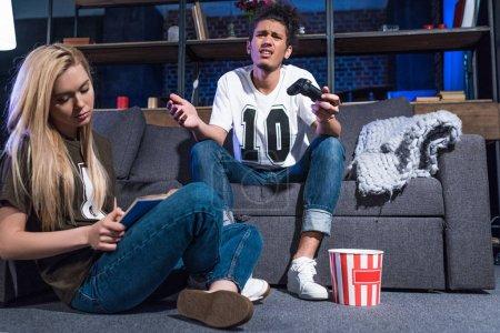 Photo pour Afro-américain homme jouer jeu vidéo tandis que caucasien copine lecture livre près de chez vous - image libre de droit