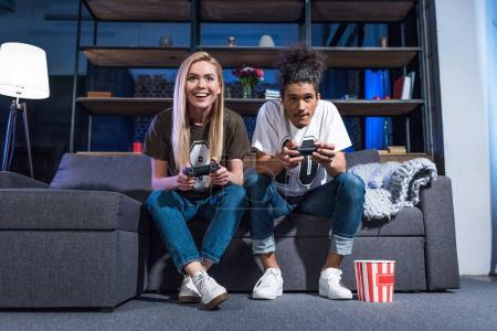 smiling multiethnic couple playing video game together at home