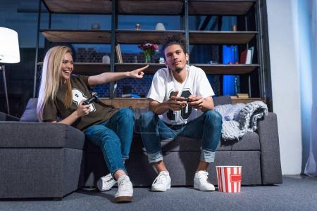 young multiethnic couple playing video game together at home