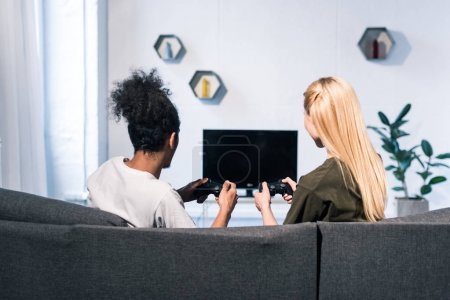 back view of multiethnic couple playing video game together at home