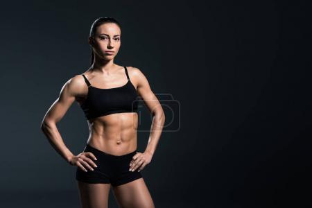 beautiful sexy female bodybuilder posing in black sportswear,  isolated on grey