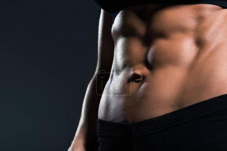Photo for Partial view of sexy female bodybuilder with muscular abs,  isolated on grey - Royalty Free Image