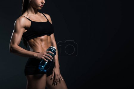 cropped view of muscular bodybuilder in sportswear with sport bottle, isolated on grey