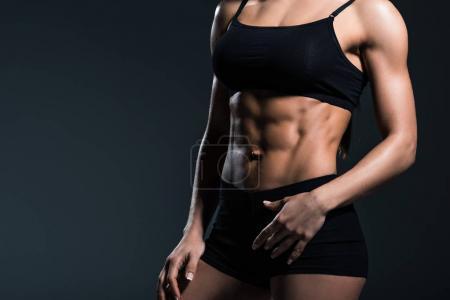 vue recadrée du bodybuilder féminin sexy avec corps musclé, isolé sur gris