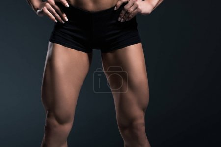 Photo for Cropped view of female bodybuilders legs, isolated on grey - Royalty Free Image
