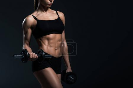 cropped view of female bodybuilder exercising with dumbbells, isolated on grey