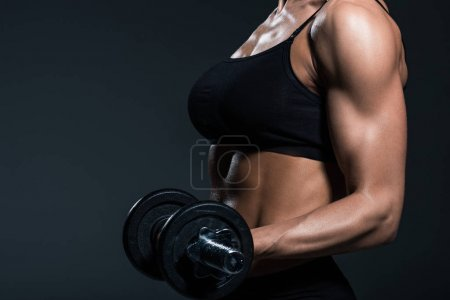 partial view of sexy sportswoman exercising with dumbbells, isolated on grey