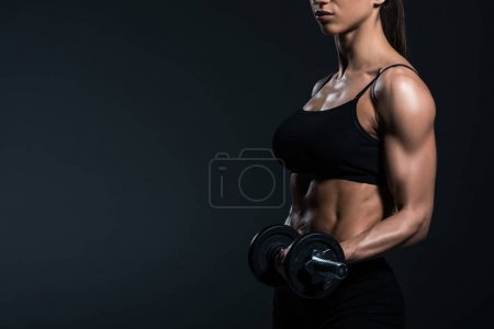 cropped view of female bodybuilder training with dumbbells, isolated on grey