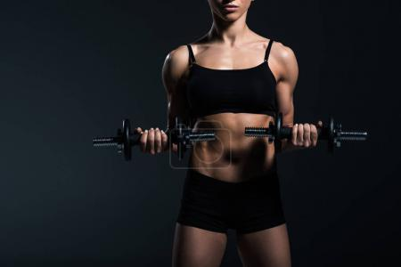 cropped view of female bodybuilder working out with dumbbells, isolated on grey
