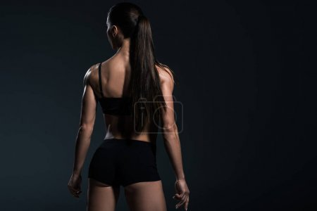 Photo for Rear view of female bodybuilder posing in black sportswear,  isolated on grey - Royalty Free Image