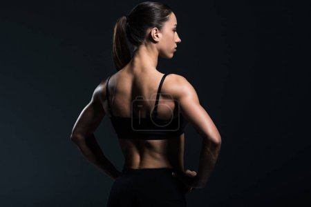 Photo for Back view of beautiful bodybuilder with muscular body in sportswear,  isolated on grey - Royalty Free Image