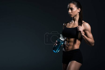 Photo for Beautiful muscular sportswoman with water in sport bottle, isolated on grey - Royalty Free Image
